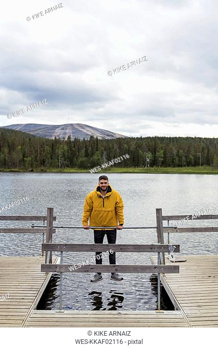 Finland, Lapland, man balancing on rod on jetty above a lake