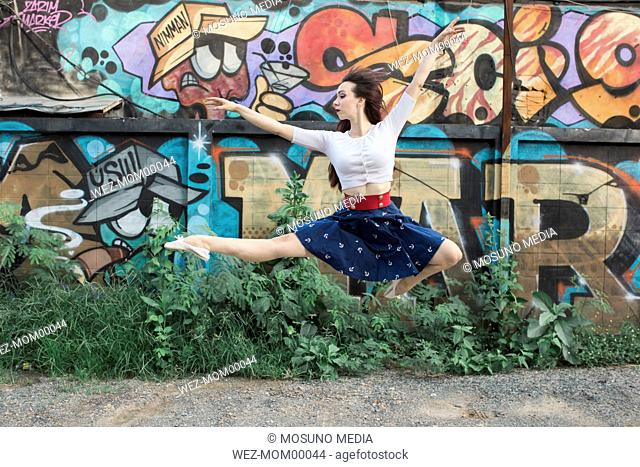 Ballerina jumping against graffiti wall
