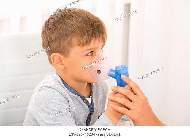 Close-up Of A Little Boy Inhaling Through Oxygen Mask In Clinic