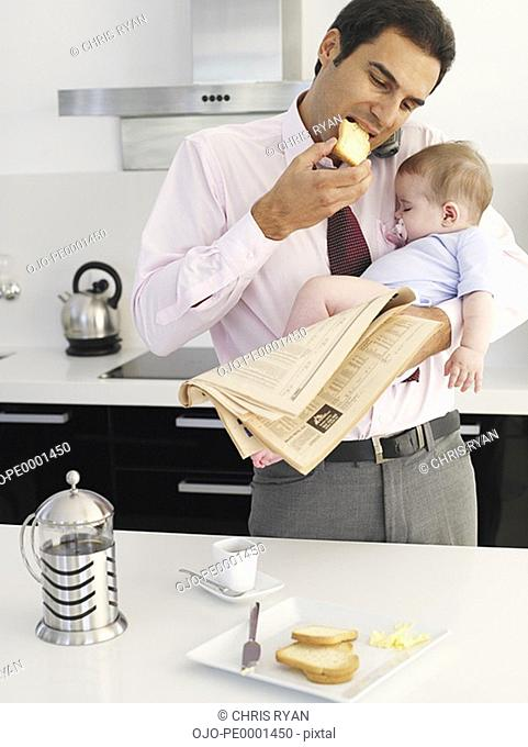 Father eating toast while holding baby daughter in a kitchen