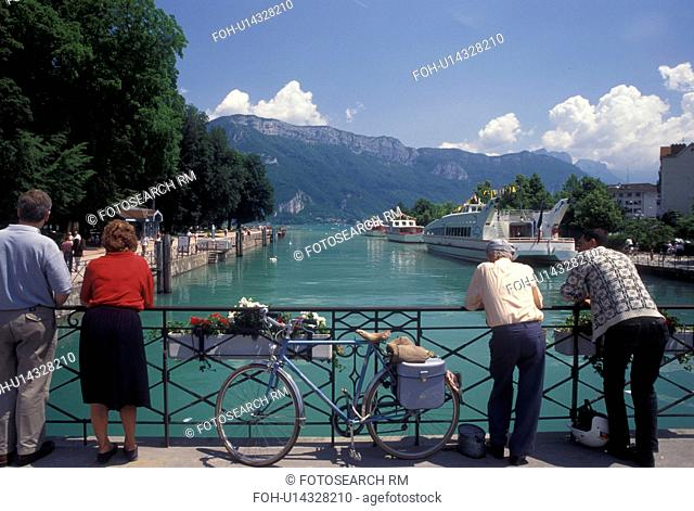 Annecy, France, Haute-Savoie, Rhone-Alpes, Europe, People looking at scenic Thiou canal and Lake Annecy (Lac d' Annecy) from bridge on the waterfront in Annecy