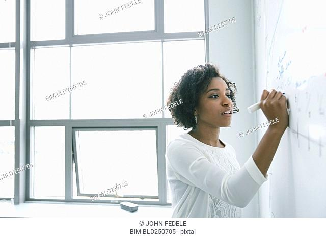 African American businesswoman writing on whiteboard in meeting
