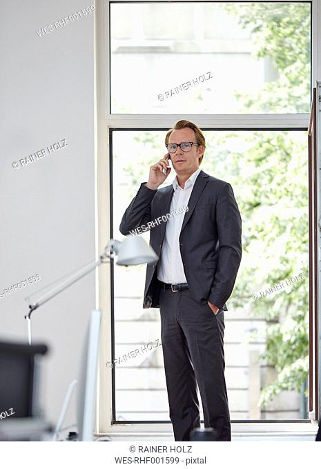 Businessman in his office standing in front of open window telephoning with smartphone