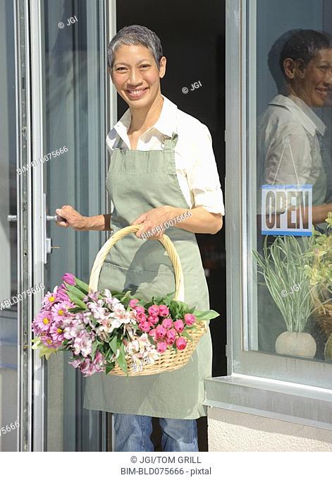Chinese florist holding basket of flowers in doorway