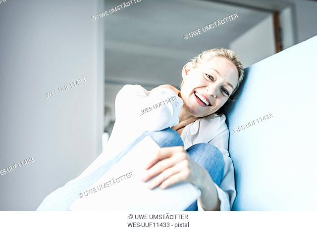 Laughing woman sitting on couch holding tablet