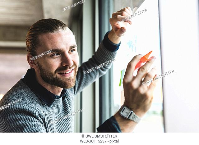 Smiling young businessman working on data at windowpane