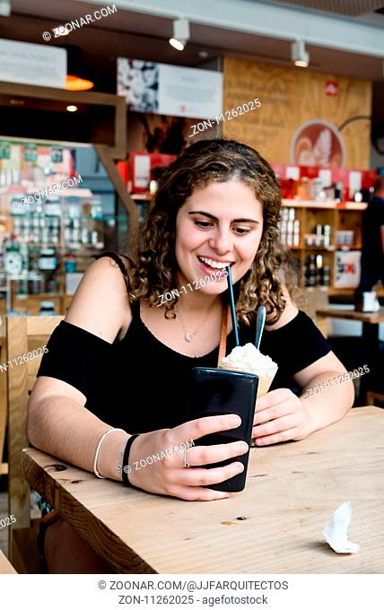 Happy girl laughing drinking ice coffe and texting on her phone. Lifestyle, joy, technology. Focus on phone
