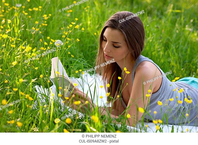 Young woman reading in field of buttercups