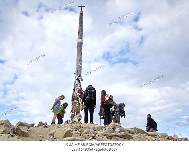 Pilgrims leaving stones at the base of Cruz de Ferro near the village of Foncebadon along the Camino de Santiago