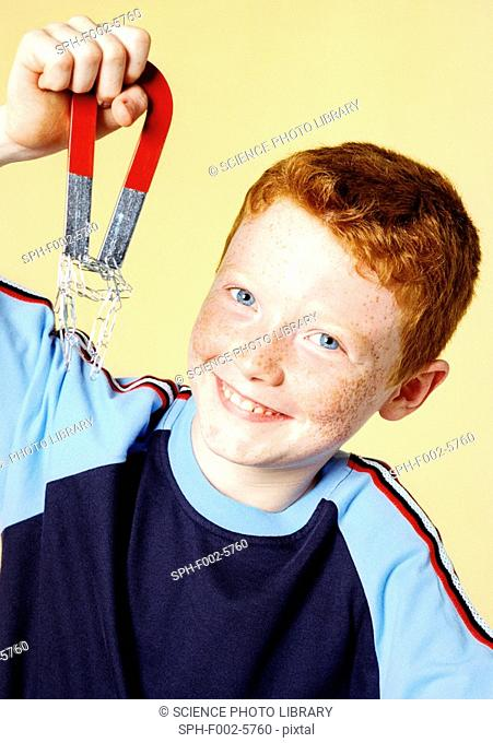 Boy lifting paperclips with a magnet