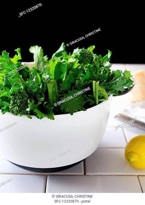 Broccolini in a white bowl, with a lemon and block of parmesan beside it