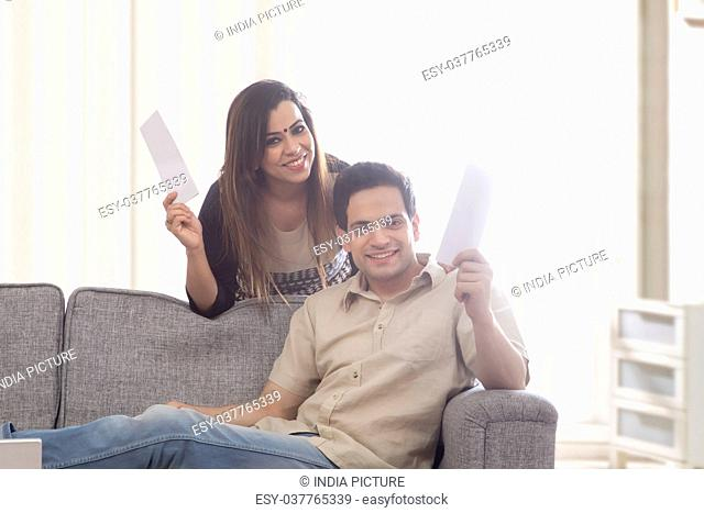 Couple cheering with home finances paper