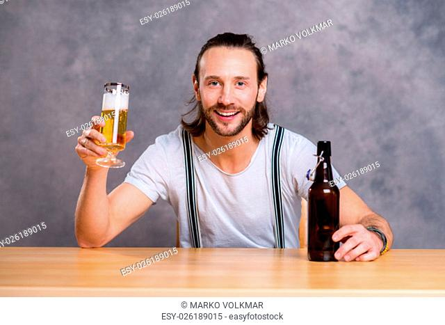 young man in front of gray background drinking beer