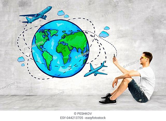 Young man in interior with creative globe and tourism sketch