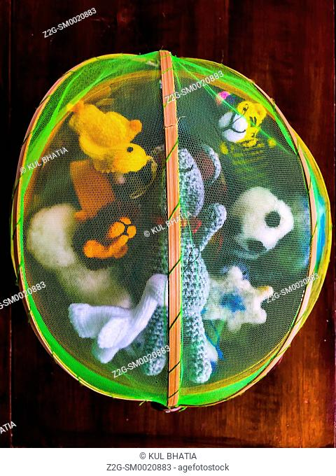 Finger puppets and other small toys in a Colorful bamboo basket covered in green mesh, Nova Scotia, Canada