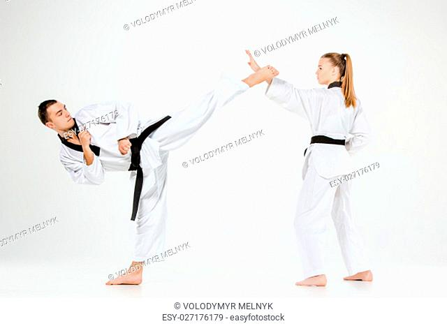 The karate girl and boy in white kimono and black belt training karate over gray background