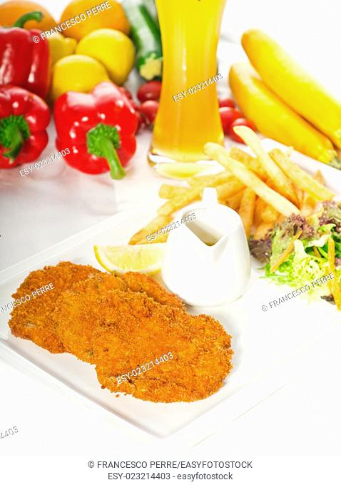 classic breaded Milanese veal cutlets with french fries, vegetables and glass of lager beer on background