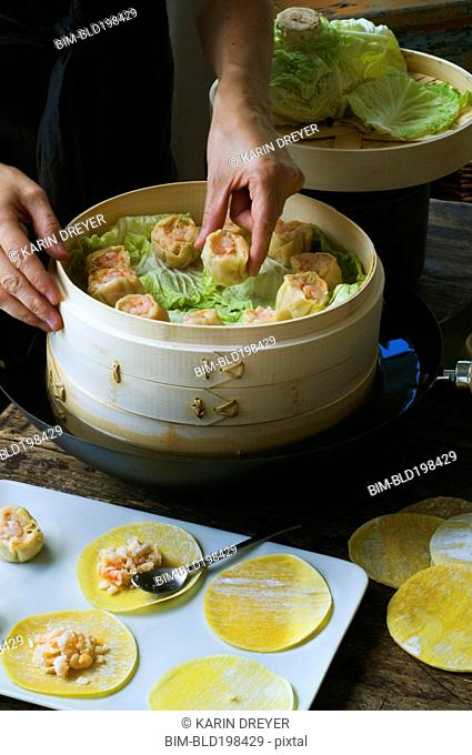Person putting Asian dumplings in steamer with cabbage