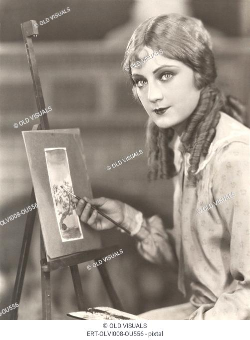 Portrait of an artist with her easel painting a picture of a tree