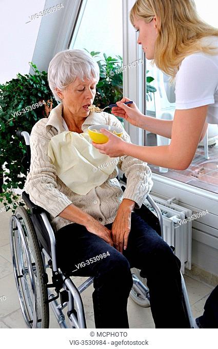 Seniorin im Rollstuhl wird von Pflegerin gefuettertModel-Released - 09/07/2009