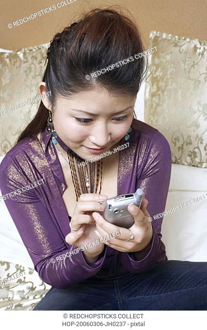 High angle view of a young woman holding a mobile phone smiling