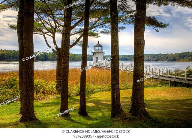 A view of the Doubling Point Lighthouse through the pine trees at the rear of keepers house. Doubling Point Light sits on the Kennebec River in Arrowsic, Maine
