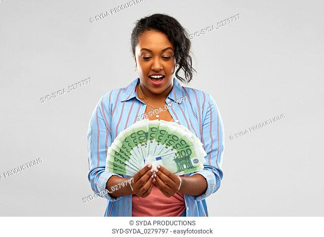 surprised african american woman with euro money
