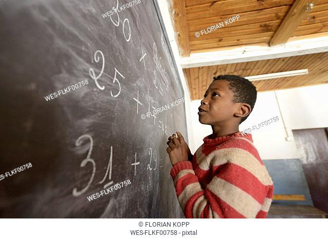 Madagaskar, Boy in Fianarantsoa elementary school calculatiing at blackboard
