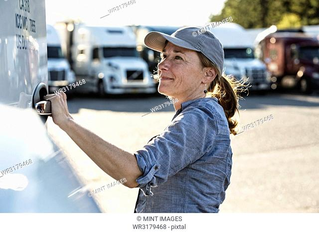 Caucasian female truck driver getting into her truck parked in a lot at a truck stop
