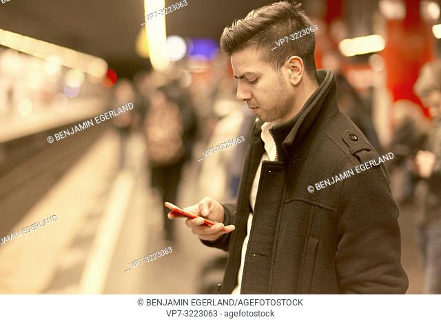 young man using mobile phone in underground train station, Afghan ethnicity, in Munich, Germany
