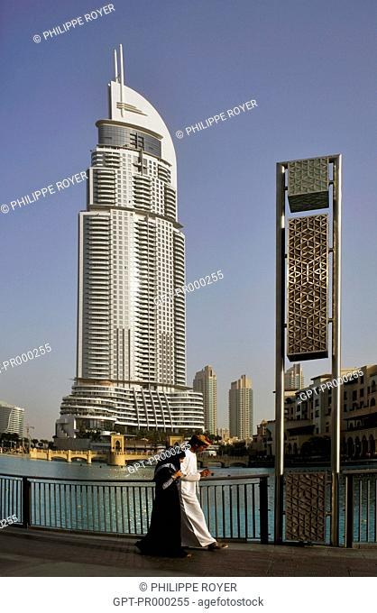 MUSLIM COUPLE PASSING IN FRONT OF THE ADDRESS DOWNTOWN DUBAI, 306-METRE HIGH SKYSCRAPER, LUXURY HOTEL AND LEISURE CENTER, DUBAI, UNITED ARAB EMIRATES