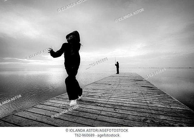 Children playing and fishing on the pier  Delta del Ebro Catalonia