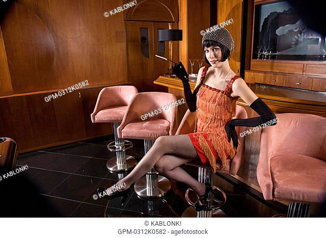 Portrait of woman in flapper dress sitting at bar with cigarette in the 1920s