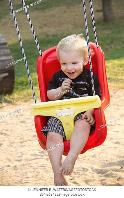 A toddler on a child swing in Priest Lake, Idaho, USA