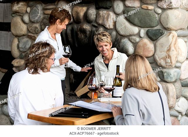 Four friends enjoy a glass of wine and conversation while waiting for a table at Sobo's, an upscale eatery in Tofino, Tofino, Vancouver Island, British Columbia