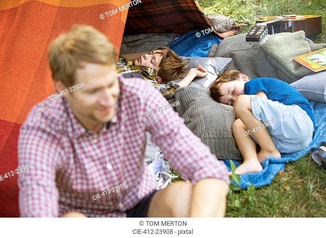 Father sitting with sleeping sons at camping tent