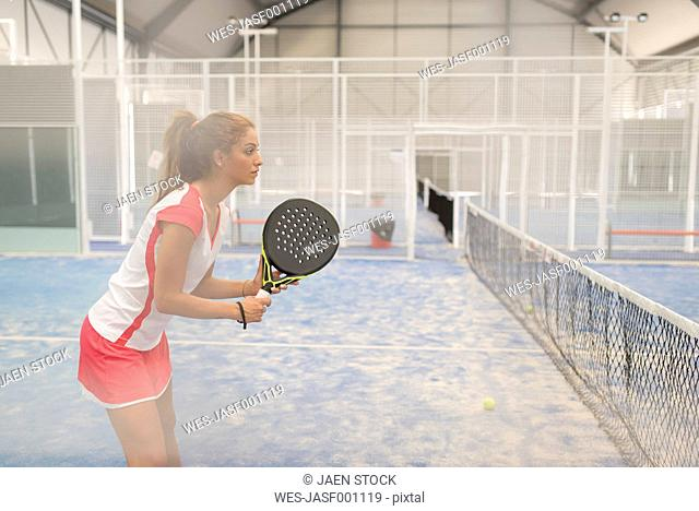 Concentrated female paddle tennis player on court
