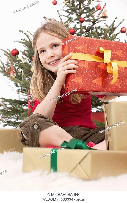 Girl sitting on carpet with gifts, christmas tree in background