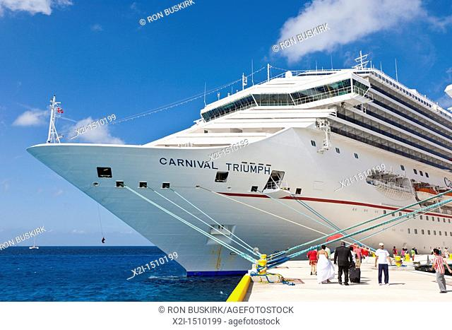 Cruise ship passengers including a just married couple in wedding dress on pier disembarking from Carnival cruise ships Triumph and Ecstasy in Cozumel