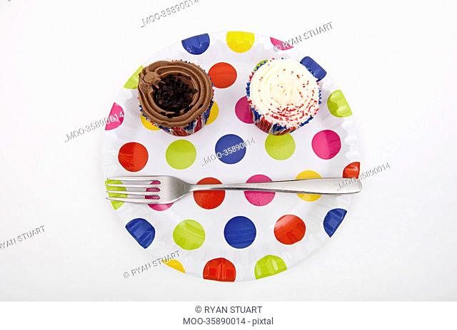 Top view of cupcakes in multicolored plate over white background