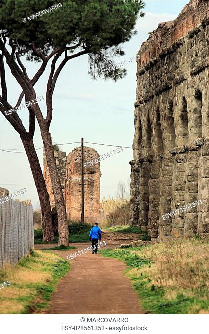 ROME, ITALY , man walking along the ancient ruins of the Roman acqueduct at the Parco degli Acquedotti public park