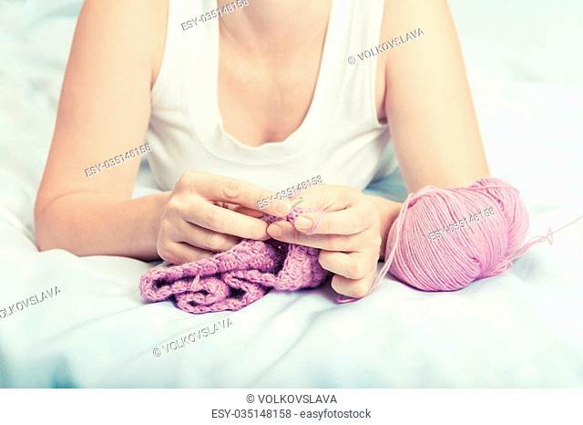 Young woman on bed crochet wool. Needlework hobby