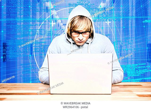 Hacker using a laptop with a blue digital background