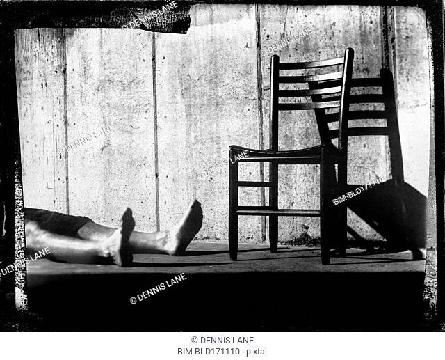 Legs laying by chair on sidewalk