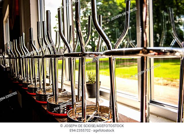Close up of the shiny metal legs of a row of bar stools upside down on a counter