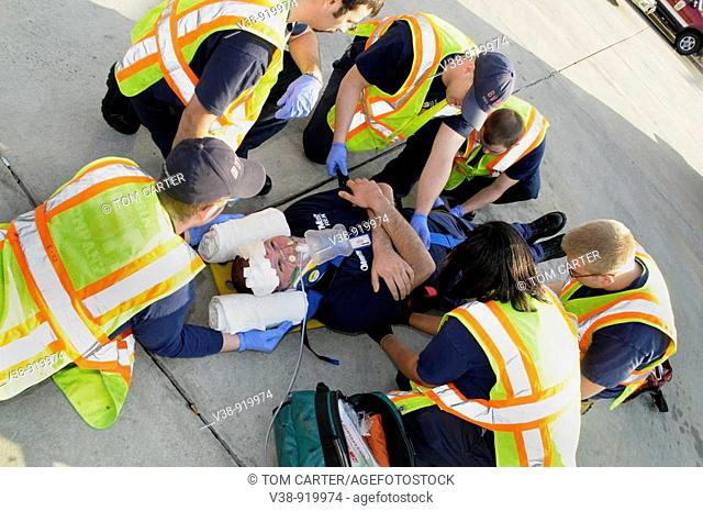 firefighters and medics work on an injured man in Bladensburg, Maryland, USA