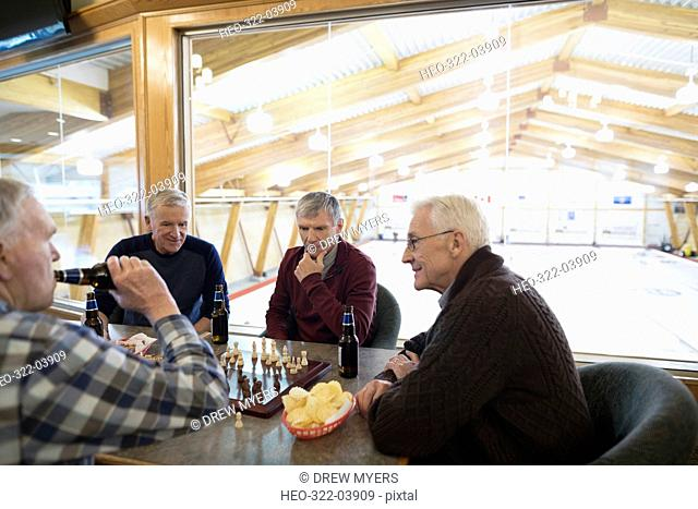 Senior men playing chess and drinking beer at curling club