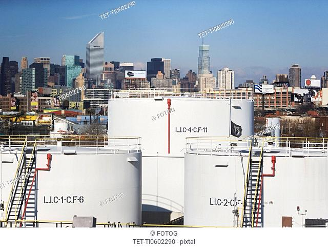 USA, New York City, Oil storage tanks in refinery with Manhattan skyline in background