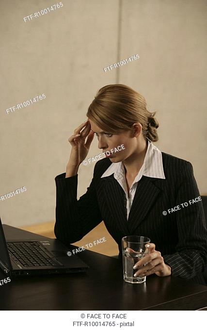 A blonde businesswoman attentively looks at her laptop while holding a glass of water