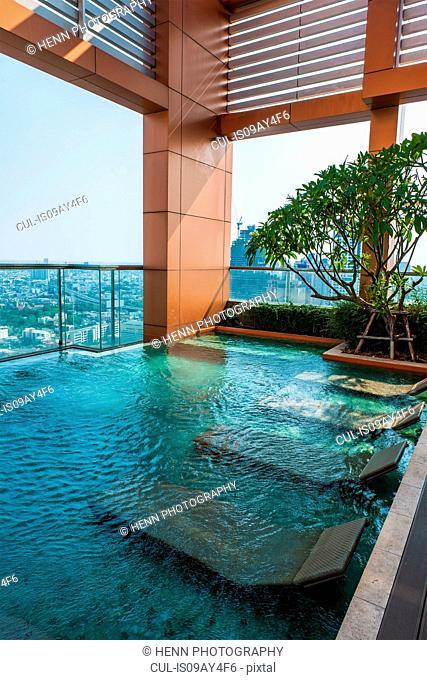 Sun loungers in swimming pool at luxury apartment, Sathorn, Bangkok, Thailand